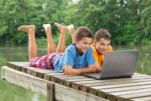 Zwei jungendliche Freunde mit Notebook am idyllischen Teich